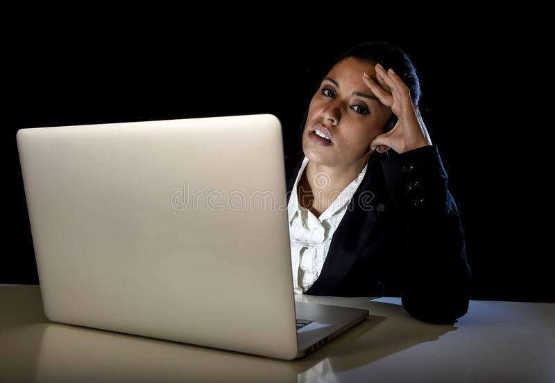 Young business woman or student girl working in darkness on laptop computer late at night tired. Young hispanic business woman or student girl working in royalty free stock image