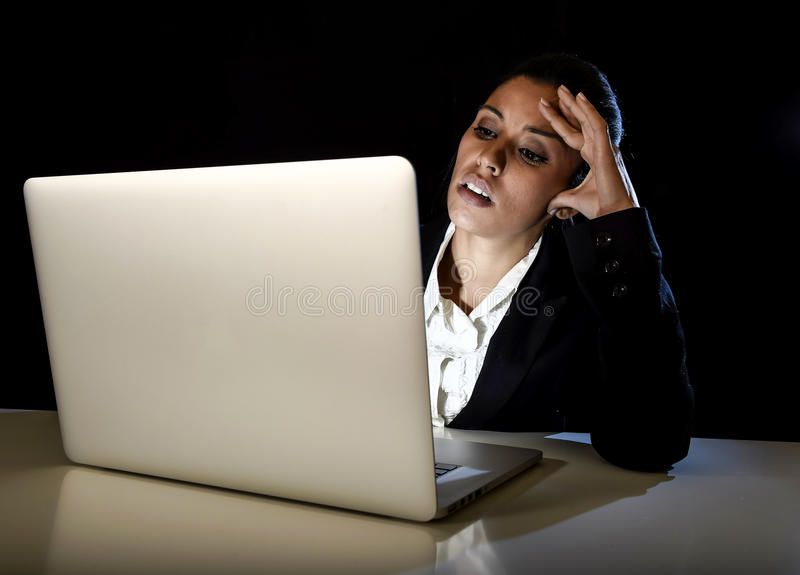 Young business woman or student girl working in darkness on laptop computer late at night tired. Young hispanic business woman or student girl working in royalty free stock photos