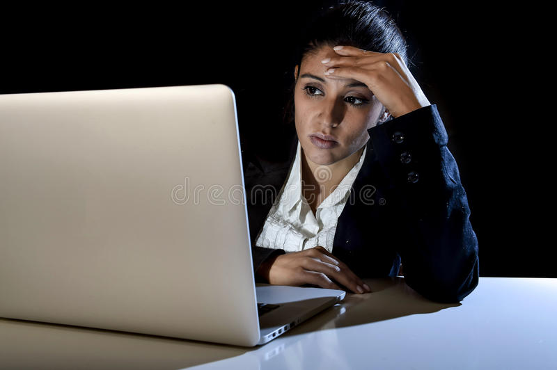 Young business woman or student girl working on laptop computer late at night bored and tired. Young latin business woman or student girl working in darkness on royalty free stock image