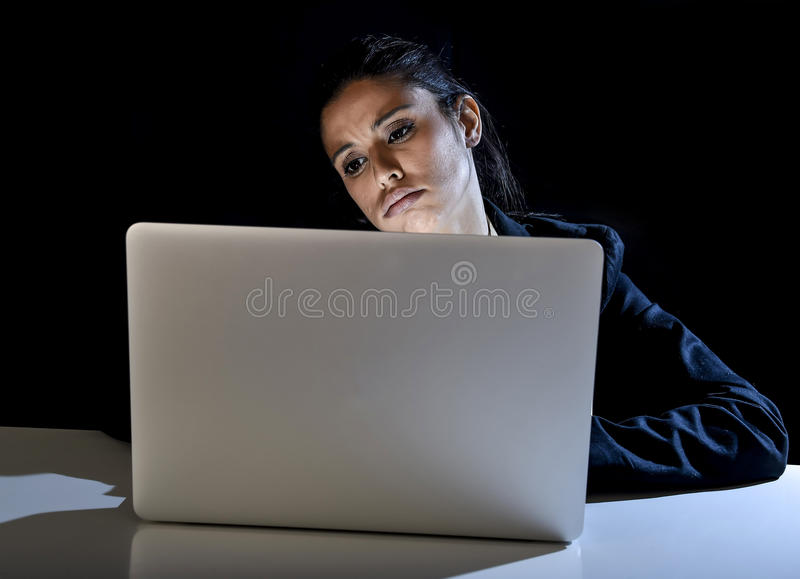 Young business woman or student girl working on laptop computer late at night bored and tired. Young spanish business woman or student girl working in darkness royalty free stock photo