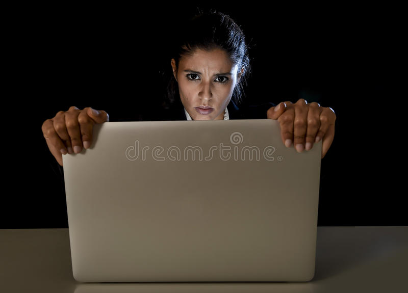 Young business woman or student girl working on laptop computer late night stressed and upset. Young business woman or student girl working in darkness holding royalty free stock images