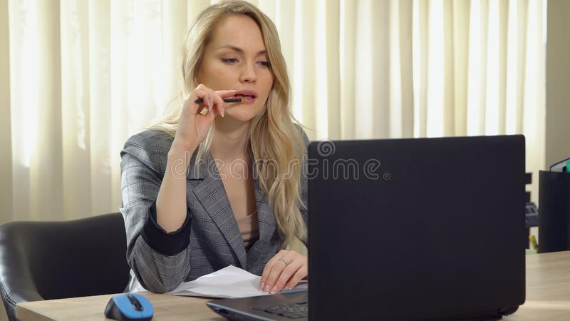 Young business woman in suit works at the computer in office. stock image