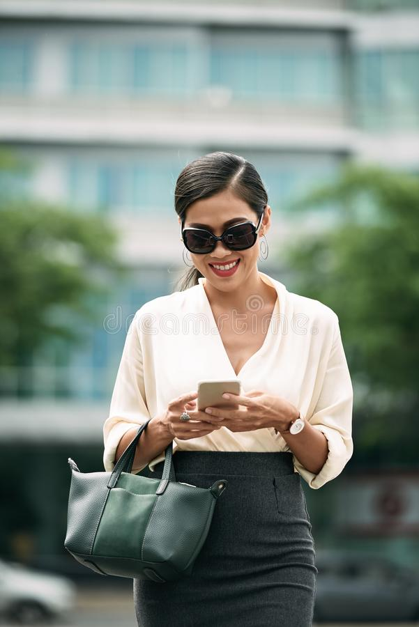 Checking smartphone. Young business woman in sunglasses smiling when reading message in her smartphone stock photography