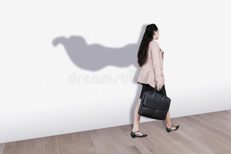 Young business woman with superhero cape shadow royalty free stock images