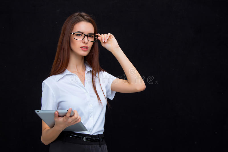 The young business woman with tablet on black background stock photography
