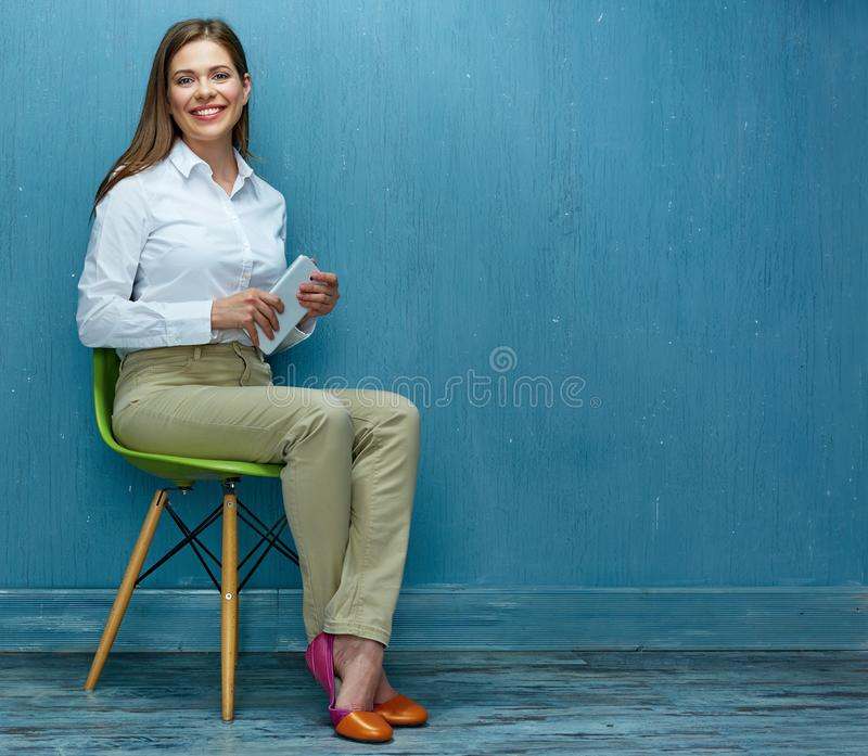 Young business woman with tablet sitting on chair. White shirt. Blue wall stock photos