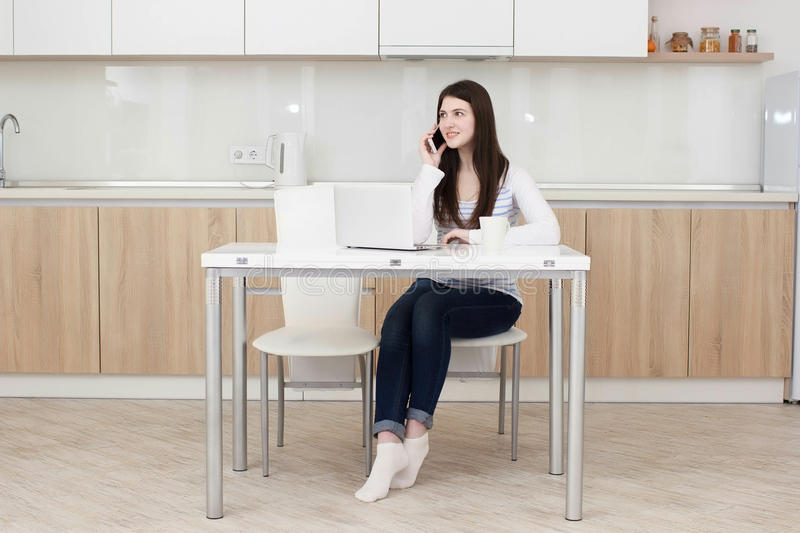 Young business woman talking on the phone while sitting at the table. stock photo