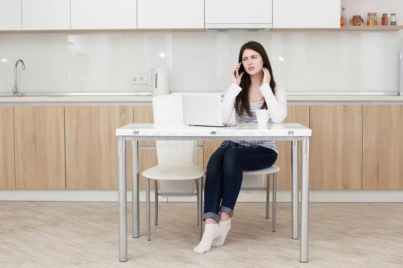 Young business woman talking on the phone while sitting at the table. royalty free stock photo