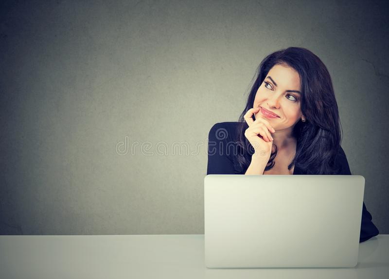 Business woman thinking daydreaming sitting at desk with laptop computer stock photos