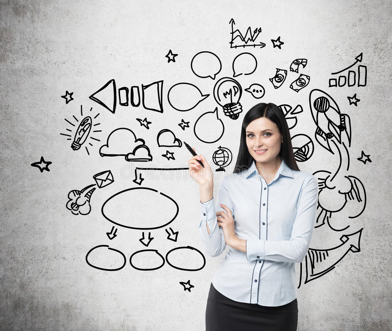 Young business woman is thinking about optimisation of social media process. Chalk icons are drawn on the concrete wall. royalty free stock images