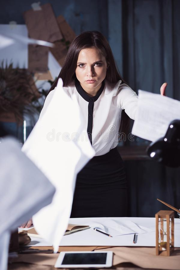 Young business woman throwing documents at camera. Disappointed and annoyed by unsuccessful project royalty free stock images