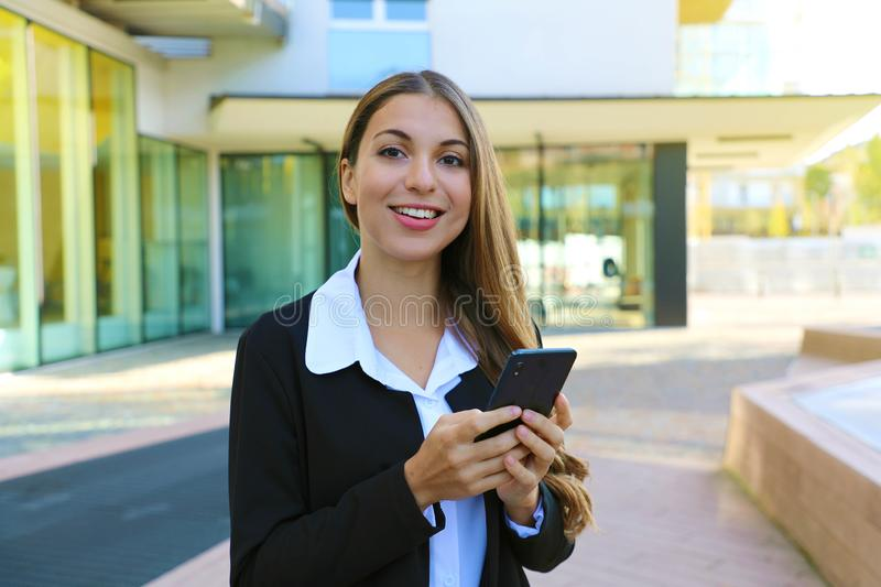 Young business woman using smart phone outdoor looking at camera royalty free stock images