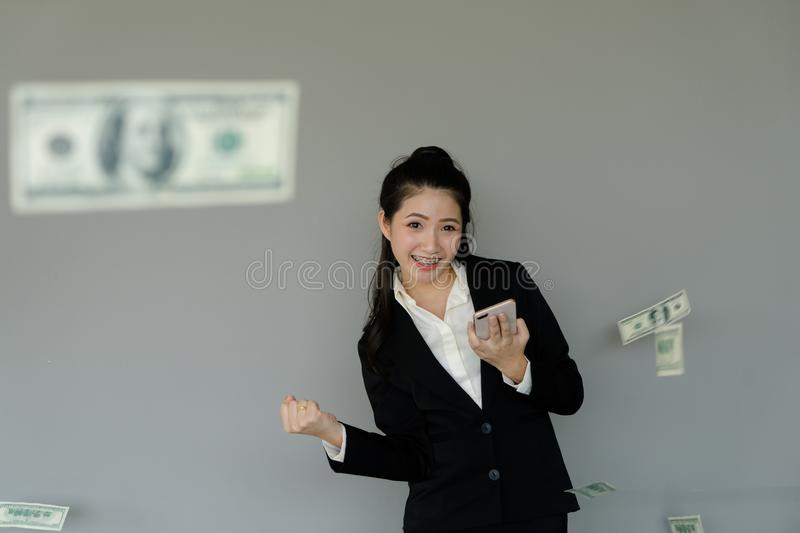 Young business woman using smart phone to make money, dollar flo royalty free stock photo