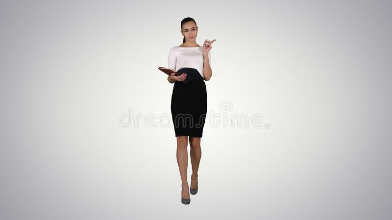 Young business woman walking and reading from notebook on gradient background. royalty free stock photos