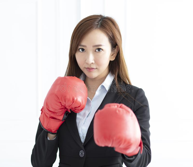 Business woman wearing boxing gloves ready to fight. Young Business woman wearing boxing gloves ready to fight stock photos
