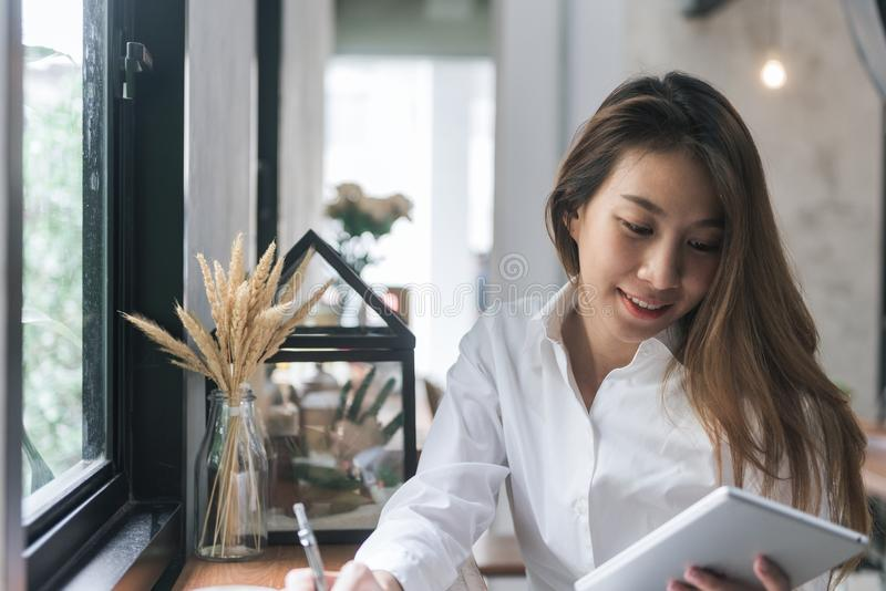 Young business woman in white dress sitting at table in cafe and writing in notebook. Asian woman using tablet and cup of coffee. royalty free stock images