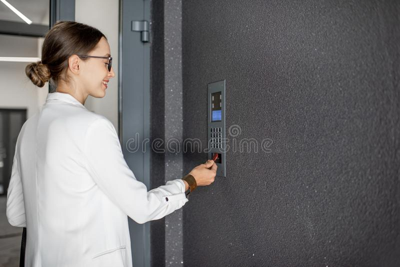 Woman opening the door with keychain. Young business woman in white suit touching the intercom with keychain opening the door of reential modern building stock photos