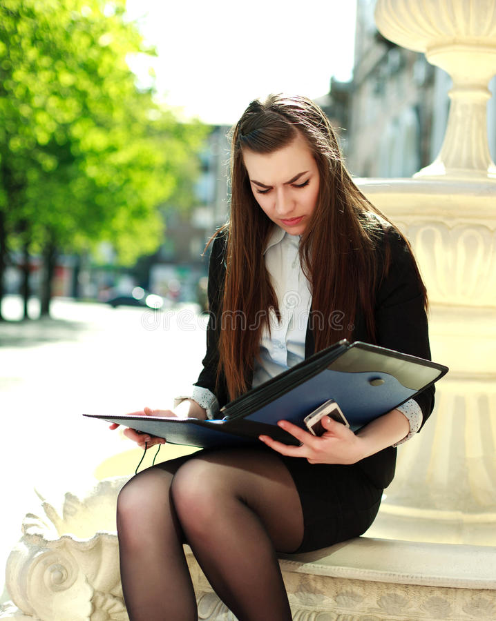 Young business woman working with a folder of documents. Sitting in the park summer day stock images