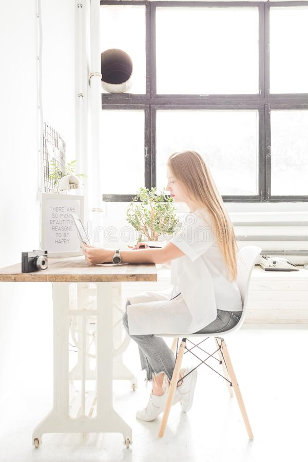 Young business woman working at home behind a laptop. Creative Scandinavian style workspace.  royalty free stock photography