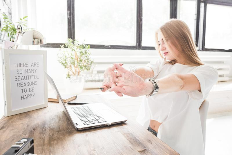 Young business woman working at home behind a laptop and stretching her hands. Creative Scandinavian style workspace.  royalty free stock photography