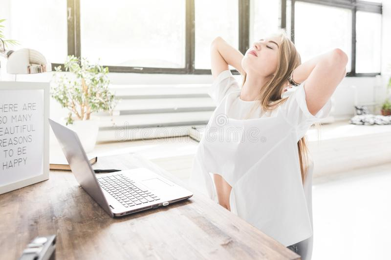Young business woman working at home behind a laptop and stretching her hands. Creative Scandinavian style workspace.  royalty free stock images