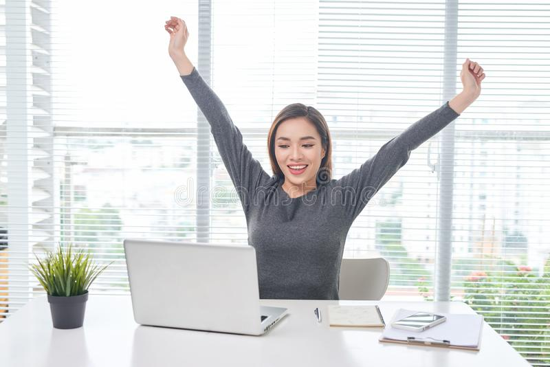 Young business woman working at home behind a laptop and stretching her hands. Creative Scandinavian style workspace royalty free stock image