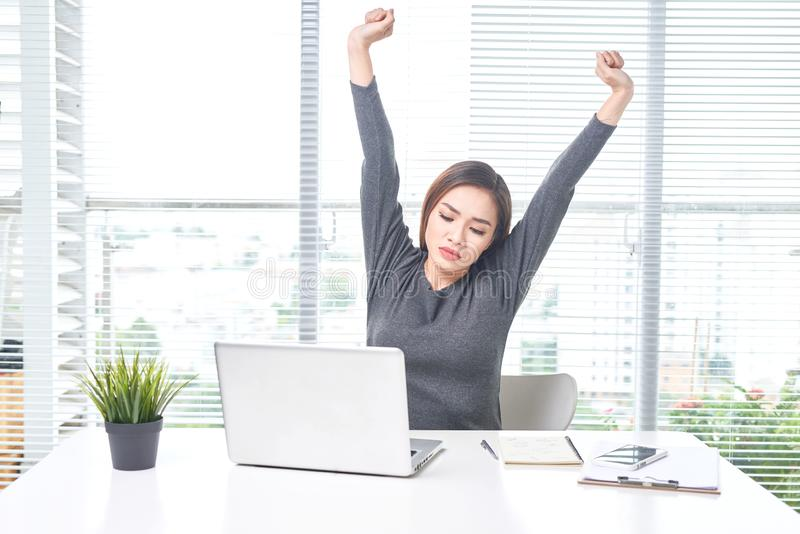 Young business woman working at home behind a laptop and stretching her hand royalty free stock photos