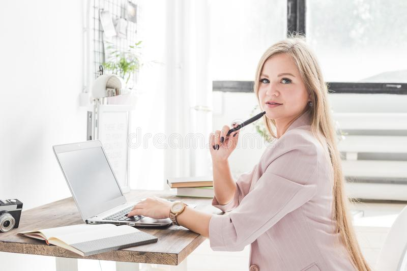 Young business woman working at home. Creative Scandinavian style workspace.  royalty free stock image