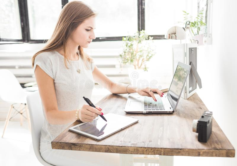 Young business woman working at home and draws on the tablet. Creative Scandinavian style workspace.  stock image