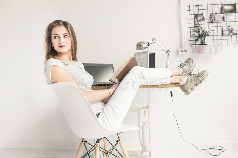 Young business woman working at home and reading a book with her legs on the table. Creative Scandinavian style. Young business woman working at home and reading royalty free stock images