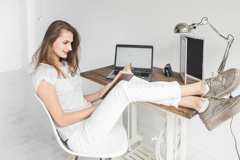 Young business woman working at home and reading a book with her legs on the table. Creative Scandinavian style. Young business woman working at home and reading stock photo
