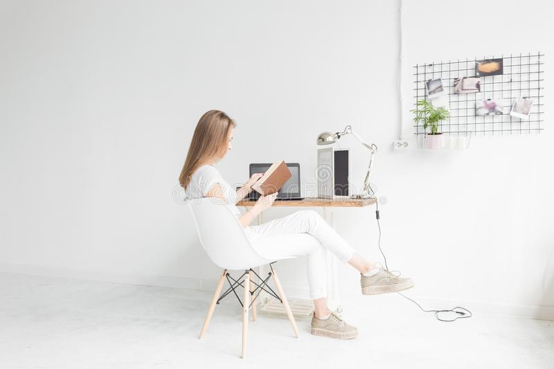 Young business woman working at home and reading a book. Creative Scandinavian style workspace.  royalty free stock image