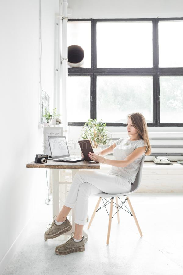 Young business woman working at home and reading a book. Creative Scandinavian style workspace.  stock photography