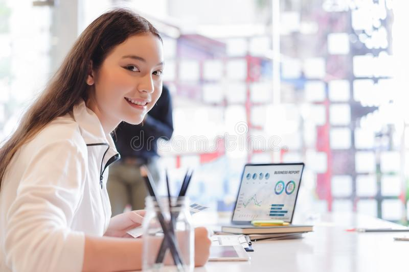 Young business woman working with laptop and analyzing business report document in co-working or coffee shop. Business people work royalty free stock photos