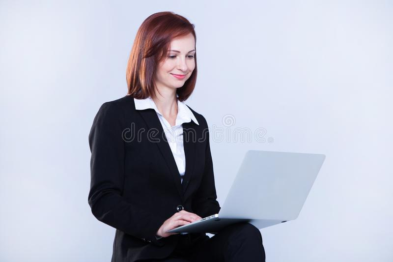 Young business woman working on laptop. Attractive mature businesswoman working on laptop stock images