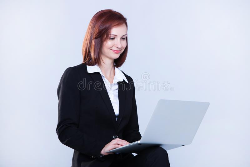 Young business woman working on laptop. Attractive mature businesswoman working on laptop royalty free stock images
