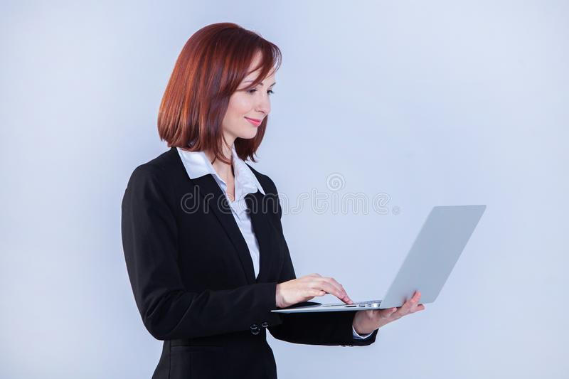 Young business woman working on laptop. Attractive mature businesswoman working on laptop stock photo