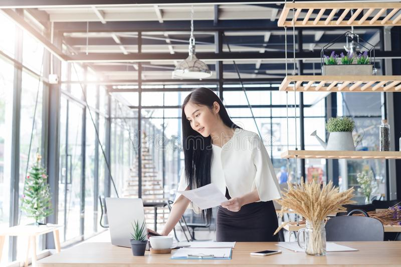 Young business woman working on laptop in cafe royalty free stock image