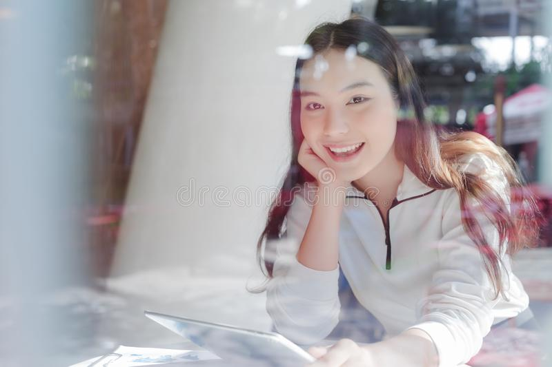 Young business woman working with tablet and analyzing business report document in co-working or coffee shop. Business people work royalty free stock photo