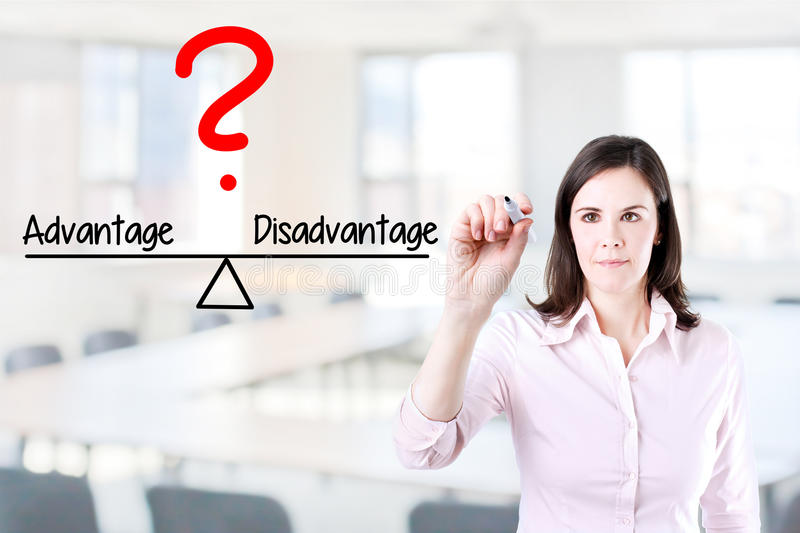 Young business woman writing advantage and disadvantage compare on balance bar. Office background. Young business woman writing advantage and disadvantage royalty free stock photography