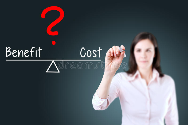 Young business woman writing cost and benefit compare on balance bar. Blue background. stock photos