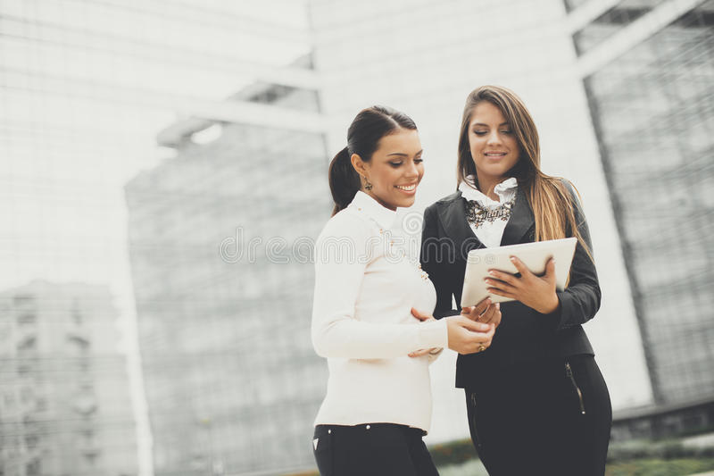 Young business women in front of office building. Business women in front of office building royalty free stock image