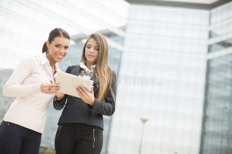 Young business women in front of office building. Two businesswomen in front of the office building royalty free stock photo