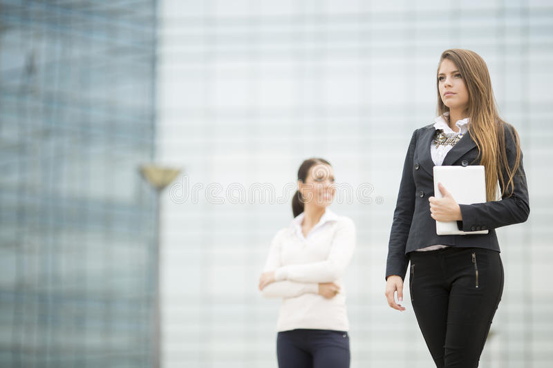 Young business women in front of office building. Two businesswomen in front of the office building royalty free stock images