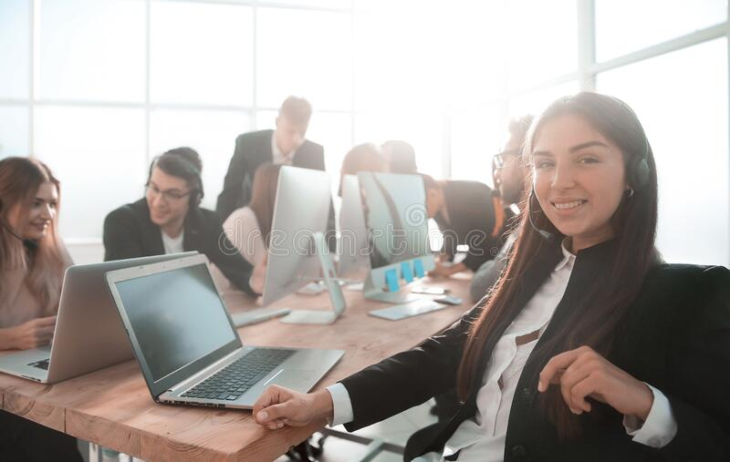 Young business woman in headset sitting at office Desk stock photography
