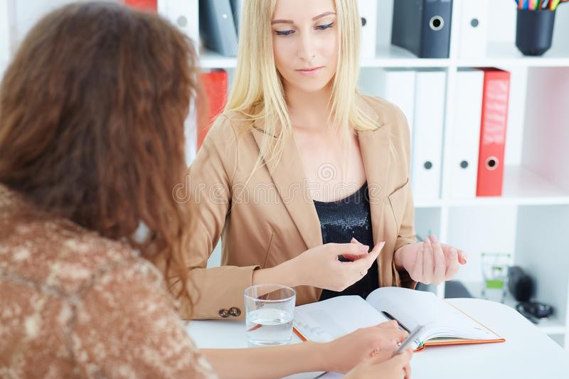 Young Caucasian business woman listening to his colleague explanations. royalty free stock images