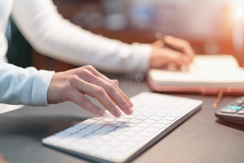Young business women typing on keyboard at office - filter applied stock images
