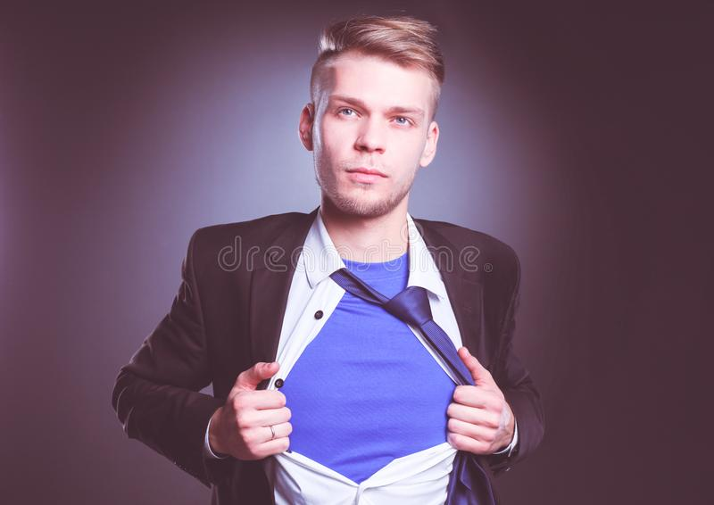 Young businessman acting like a super hero and tearing his shirt, isolated on gray background. Young businessman royalty free stock photos