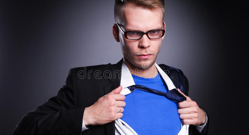 Young businessman acting like a super hero and tearing his shirt, on gray background. Young businessman acting like a super hero and tearing his shirt stock photo