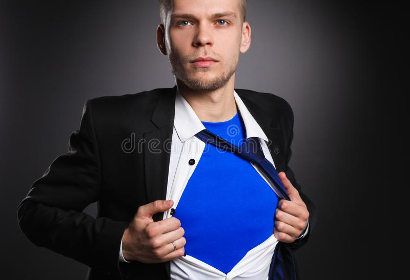 Young businessman acting like a super hero and tearing his shirt, on gray background. Young businessman acting like a super hero and tearing his shirt stock image
